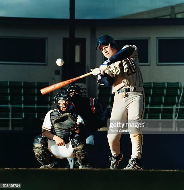 baseball player swinging at pitch - キャッチャー ストックフォトと画像