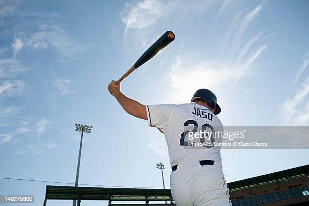 baseball player swinging bat, rear view - basebollslag bildbanksfoton och bilder