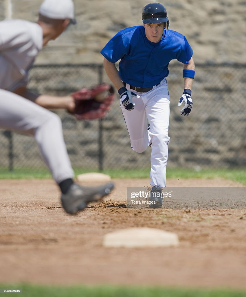 Baseball player trying to steal base : Stock Photo