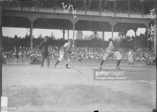 Baseball player Ty Cobb of the Detroit Tigers runs towards first base as Johnny Kling catcher for the Chicago Cubs watches during a World Series game...