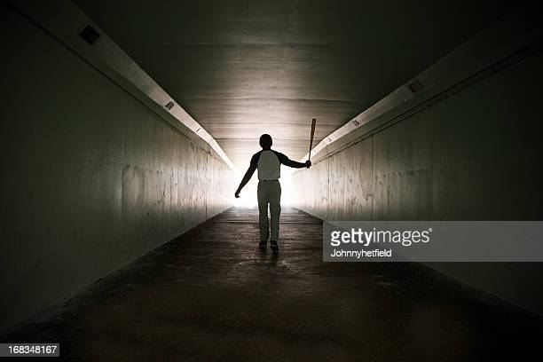 baseball player walking out of stadium tunnel swinging bat  - baseball sport stock pictures, royalty-free photos & images