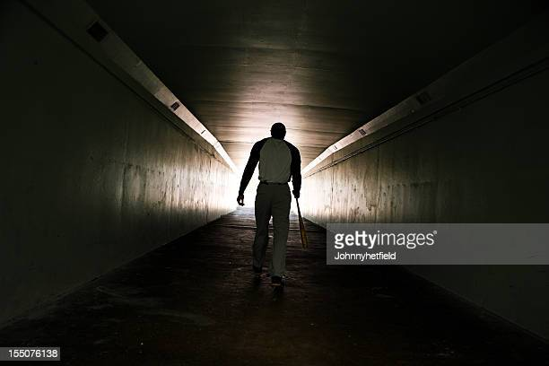 Baseball player walking with bat
