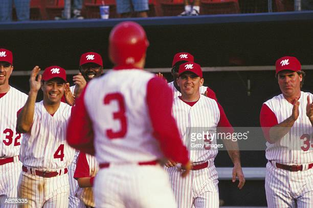 baseball players applauding team mate - baseball team stock pictures, royalty-free photos & images