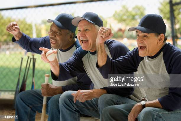 Baseball players cheering on bench