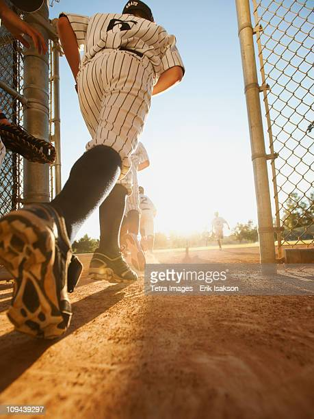 Baseball players (10-11) entering baseball diamond