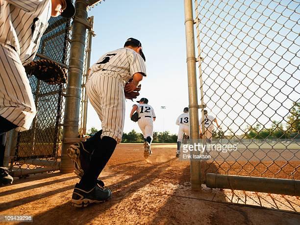 baseball players (10-11) entering baseball diamond - baseball team stock pictures, royalty-free photos & images