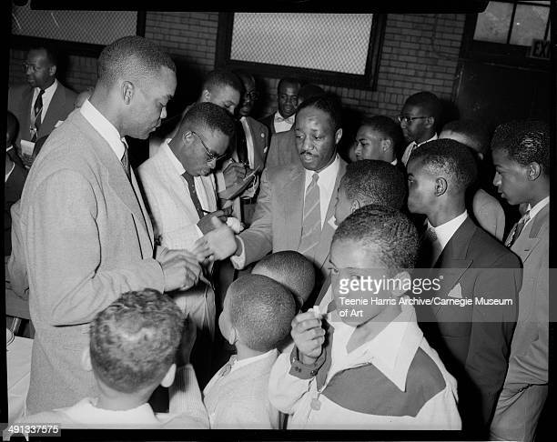 Baseball players Monte Irvin Curtis 'Curt' Roberts and Willie Mays signing autographs for boys including Barry Chapman Jimmy Benton Errol Davis Jr...