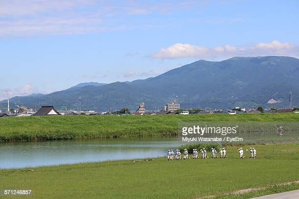 baseball players on grassy field by mountain against sky - 野球チーム ストックフォトと画像