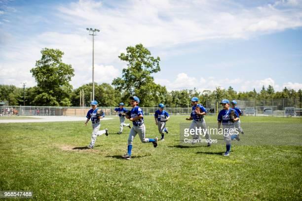 baseball players running on field against sky - 野球チーム ストックフォトと画像