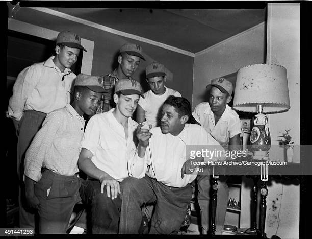 Baseball players wearing 'W' hats giving radio interview with Mal Goode in domestic interior Pittsburgh Pennsylvania circa 19501970