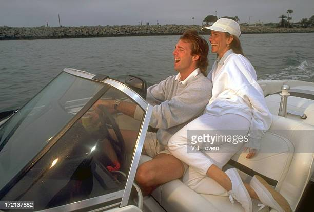 Portrait of Califonia Angels pitcher Chuck Finley casual riding in motorboat with his girlfriend actress Tawny Kitaen during photo shoot Anaheim CA J...