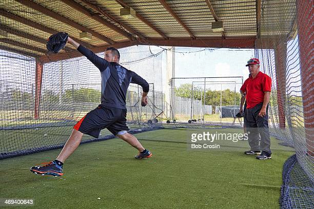 Portrait of Miami Marlins pitcher Jose Fernandez pitching as personal pitching coach Orlando Chinea looks on during training session photo shoot at...