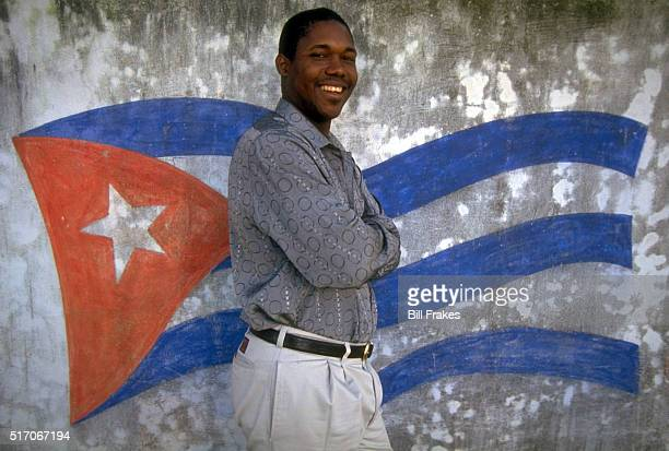 Portrait of Omar Linares posing in front of mural of Cuban national flag Havana Cuba 5/1/1995 CREDIT Bill Frakes