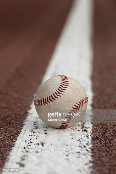 Baseball resting on a baseline.