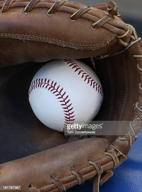 A baseball rests inside the catcher's glove of Chris Snyder of the Baltimore Orioles before the start of MLB game action against the Toronto Blue...