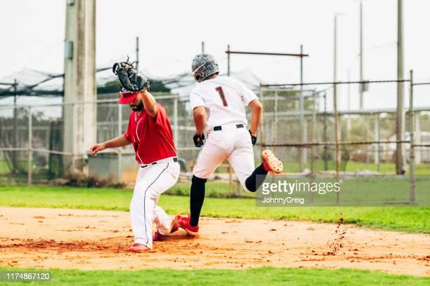 野球ランナーが一塁へ投げでバッグに触れる - 高校野球 ストックフォトと画像