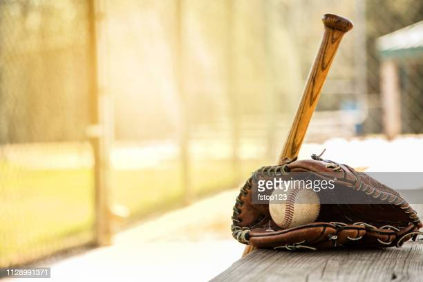 baseball season is here.  bat, glove and ball on dugout bench. - sports dugout stock pictures, royalty-free photos & images