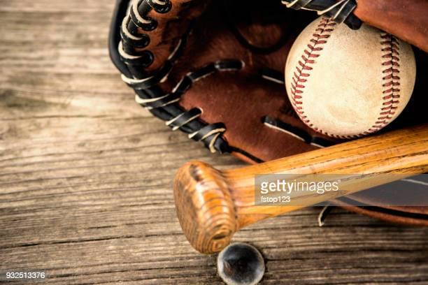 Baseball season is here.  Bat, glove and ball on dugout bench.