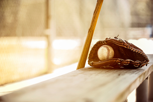 Baseball season is here.  Bat, glove and ball on dugout bench. 932515840