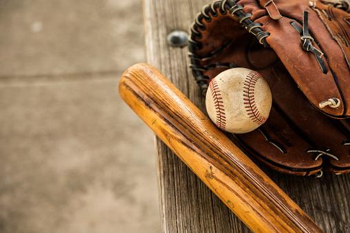 Baseball season is here.  Bat, glove and ball on dugout bench. 932515920