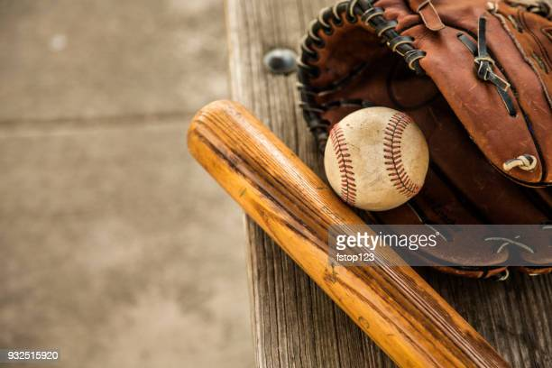Baseball season is here.  Bat, glove and ball on dugout bench.