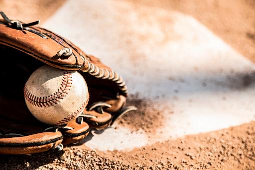 Baseball season is here.  Glove and ball on home plate. 1036826382