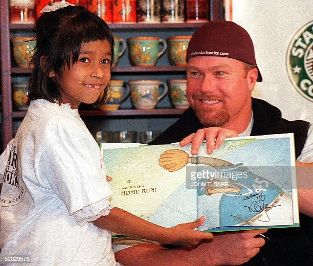 Baseball star Mark McGwire of the St Louis Cardinals holds up a book he signed for sixyear old Naureen Hug during a press event 18 February to...