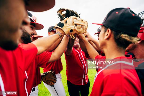 baseball team coach and players raising gloves for high-five - team sport stock pictures, royalty-free photos & images