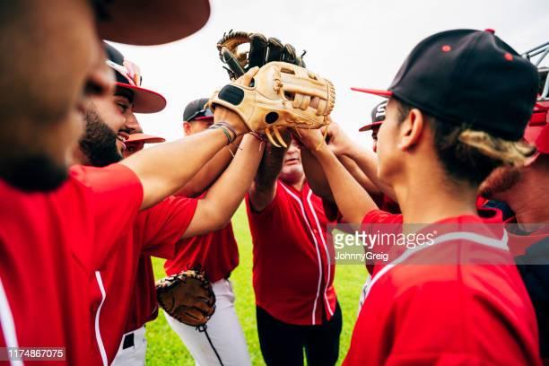 allenatore di squadra di baseball e giocatori che alzano i guanti per cinque - baseball foto e immagini stock