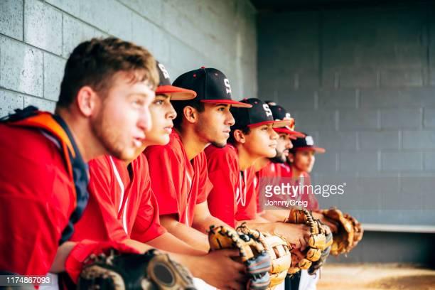 ダッグアウトに座っている野球チームのメンバーは、ゲームに焦点を当てた - 野球チーム ストックフォトと画像