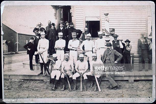 A baseball team poses with their fans on the sidewalk circa 1880 in an unknown town in South Dakota