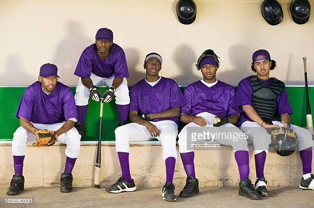 Baseball team sitting in dugout, (portrait)