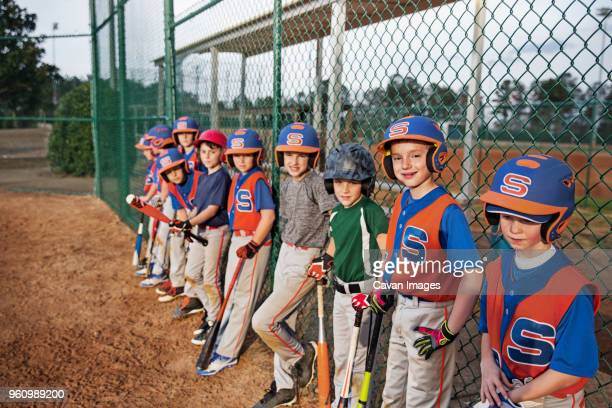 baseball team standing by chainlink fence on field - baseball team stock pictures, royalty-free photos & images