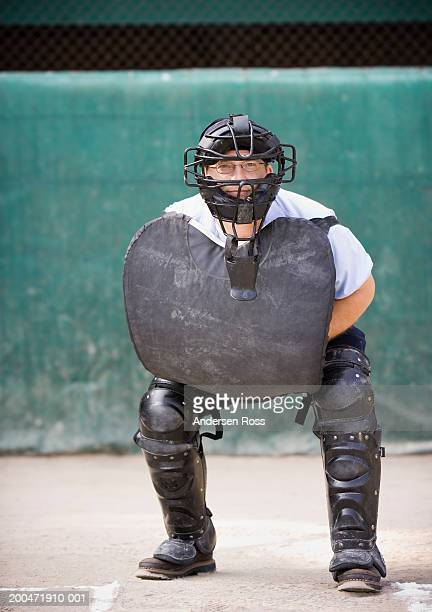 Baseball umpire crouching behind home plate, portrait