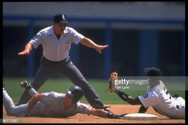 View of 2B umpire calling Cleveland Indians Omar Vizquel safe after diving back to 2B vs Chicago White Sox Ray Durham.