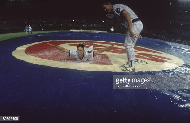 View of Chicago Cubs Greg Maddux and Les Lancaster playing slip and slide during rain delay vs Philadelphia Phillies First night game in Wrigley...