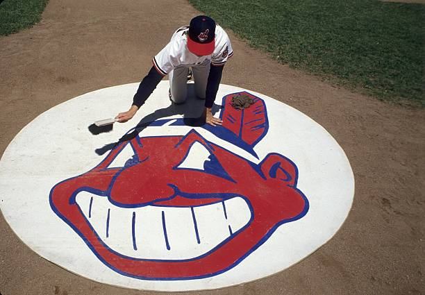 View of Cleveland Indians bat boy Dan Rocky cleaning Chief Wahoo logo of on deck batter's circle before game vs Chicago White Sox Cleveland OH...