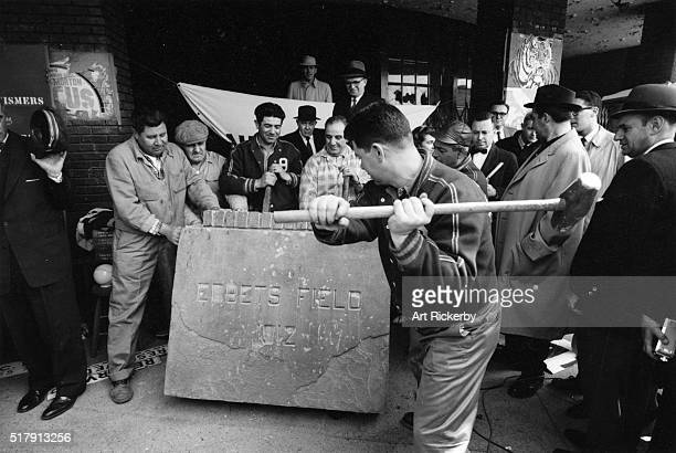View of construction worker Maxie Rosenfeld swinging sledgehammer in an attempt to open the cornerstone in preparation for a souvenir auction before...