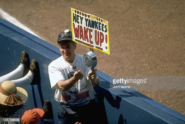 View of New York Yankees fan Freddy Sez Schuman holding FREDDY SEZ HEY YANKEES WAKE UP in stands while banging his pan with a spoon during game vs...