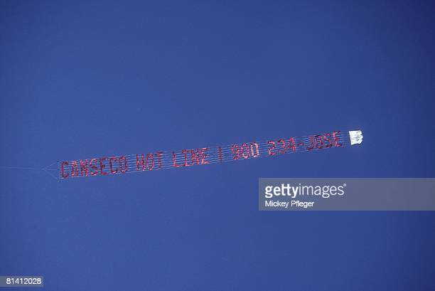 Baseball View of plane flying over Oakland Coliseum with Oakland Athletics Jose Canseco CANSECO HOT LINE banner during game Oakland CA 10/3/1989