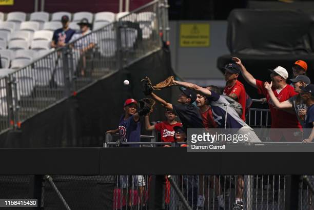 View of young fans in stands reeaching for home run ball before New York Yankees vs Boston Red Sox game at London Stadium London Series London...