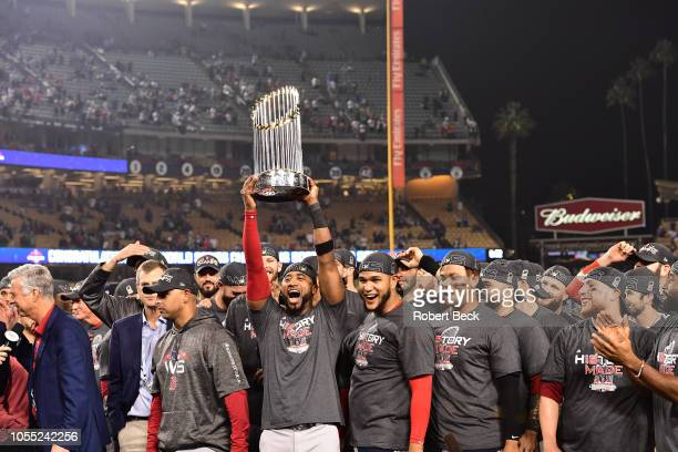 World Series Boston Red Sox Eduardo Nunez victorious holding up commissioner's trophy on field after winning game and series vs Los Angeles Dodgers...