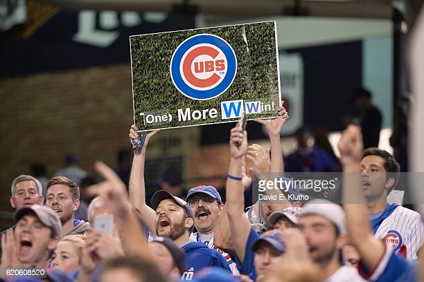 World Series Chicago Cubs fan in stands holding up sign with Cubs logo that reads ONE MORE W WIN during game vs Cleveland Indians at Progressive...