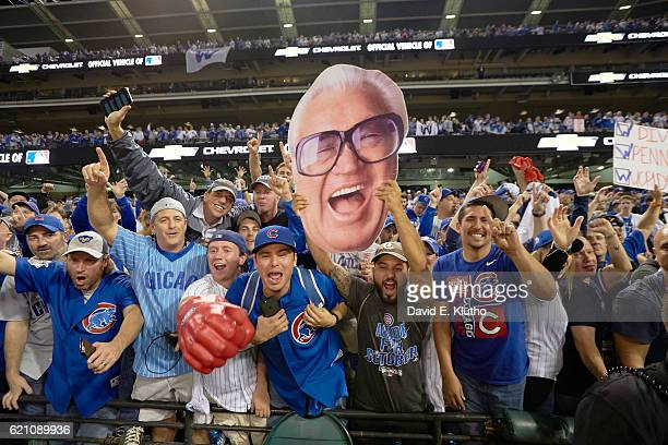 World Series Chicago Cubs fans in stands with cardboard cutout of Harry Caray's face after winning game and series vs Cleveland Indians at...