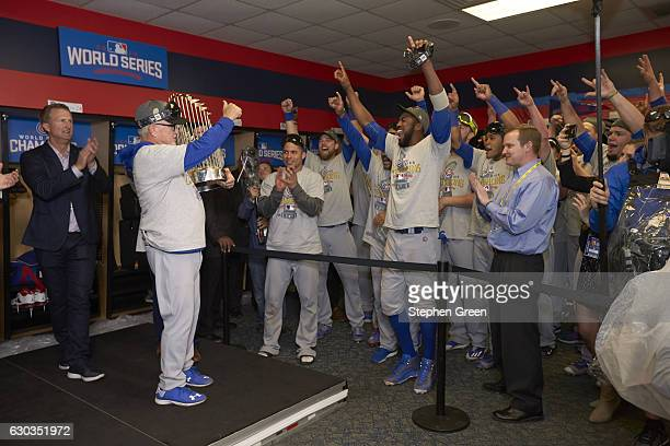 World Series Chicago Cubs manager Joe Maddon victorious holding World Series trophy in locker room after winning game and series vs Cleveland Indians...