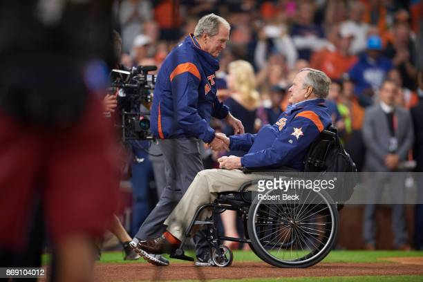World Series Former United States President George HW Bush in wheelchair on field shaking hands with his son George W Bush during ceremonial first...