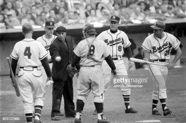 World Series Home plate umpire Augie Donatelli looking at ball in front of New York Yankees Yogi Berra and Milwaukee Braves Nippy Jones during Game 4...