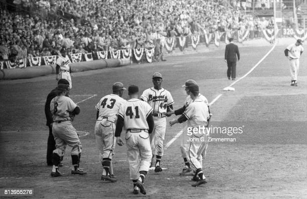 Milwaukee Braves Hank Aaron victorious with teammates after scoring run vs New York Yankees at Milwaukee County Stadium Game 3 Milwaukee WI CREDIT...