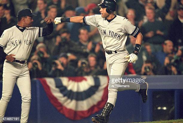 World Series New York Yankees Derek Jeter victorious with third base coach Willie Randolph after hitting home run vs New York Mets at Shea Stadium...