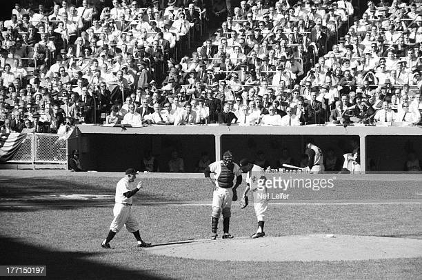 World Series New York Yankees manager Casey Stengel on field with Elston Howard and Luis Arroyo for mound visit pitching change during Game 5 vs...